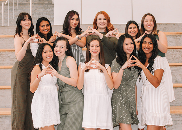 Group of women making a sorority hand symbol.