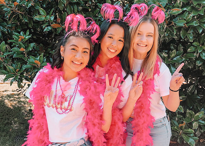 Three women with pink feather boas, holding up one,two and three fingers.