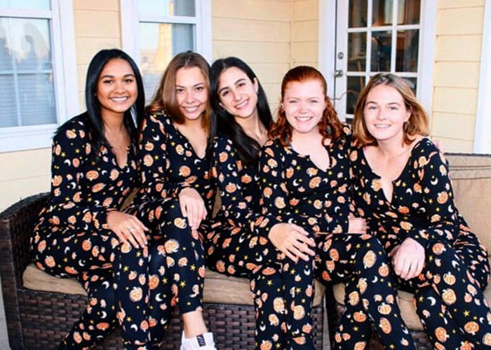 Five women posing in similar patterned outfits.