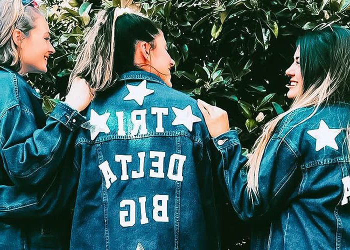 Women with denim jackets that read '三三角洲 Big' on the back.