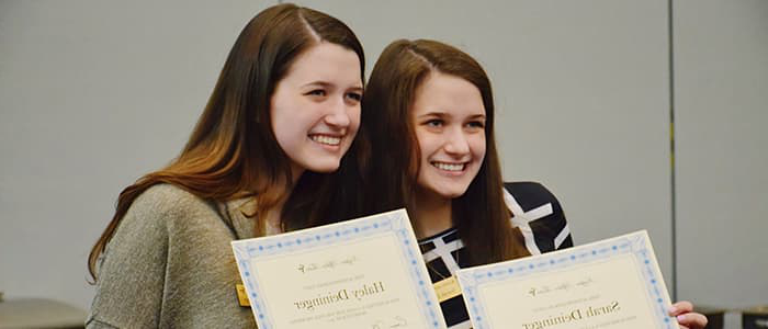 Two women posing with award certificates.