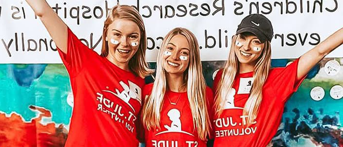 Three women posing with St. Jude Volunteer T-Shirts.
